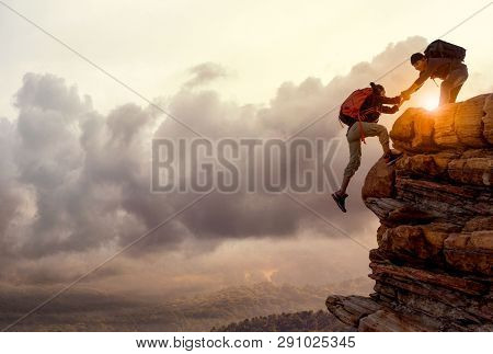 People Helping Each Other Hike Up A Mountain At Sunrise. Giving A Helping Hand, And Active Fit Lifes