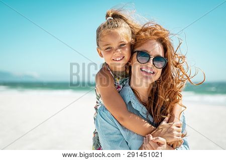 Smiling mother and beautiful daughter having fun on the beach. Portrait of happy woman giving a pigg