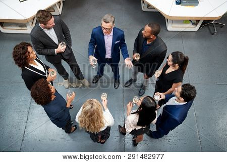 Overhead Shot Of Business Team Celebrating Success With Champagne Toast In Modern Office stock photo