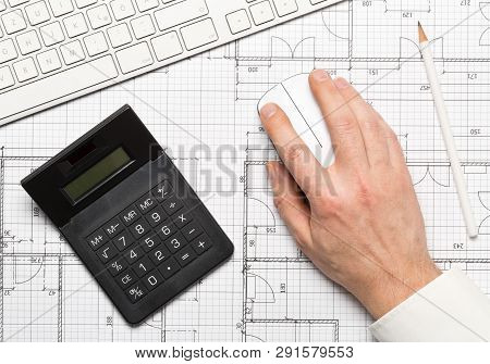 Architect using computer mouse on architectural blueprint house building plan with computer keyboard flatlay top view from above stock photo