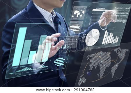 Businessman in front of virtual modern computer virtual touch screens analysing on investment risk management and return on investment analysis stock photo