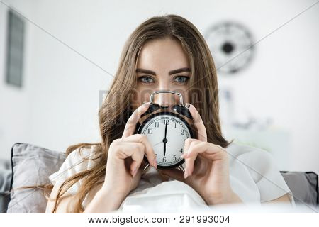 A young woman is holding an alarm clock with her hands, she is mysteriously looking at the camera. Daylight saving time concept. stock photo