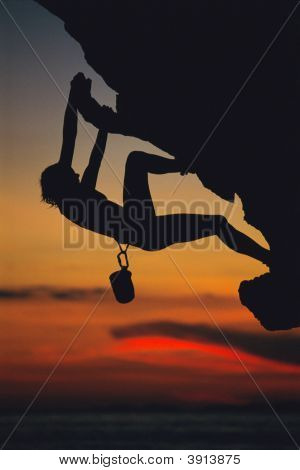 mountain climber coming up under mountain cliff (silhouette - visible graininess) stock photo