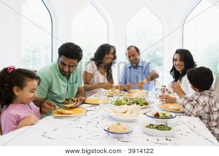Family sitting at dinner table smiling (high key) stock photo
