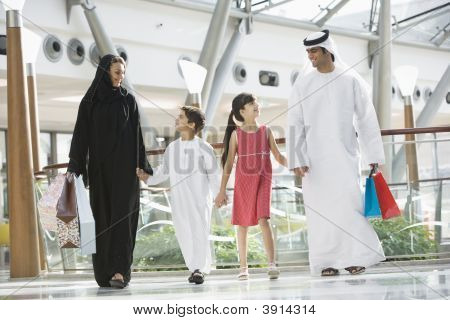 Family walking in mall holding hands and smiling (selective focus) stock photo