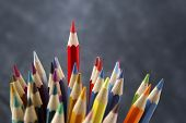 Red pencil emerging from others