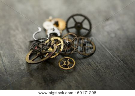 Old age gadget parts. Precession clock gears, on a old grungy metal surface. stock photo
