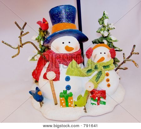 This Snowman Father and child are outside throwing snowballs by a lightpole in front of two trees. Some wrapped holiday gifts, and three little bird friends join in the celebration.  stock photo
