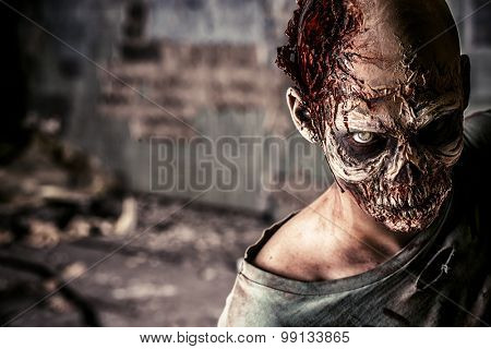 Horrible terrifying zombie man on the remains of an old house. Repulsiveness. Halloween.