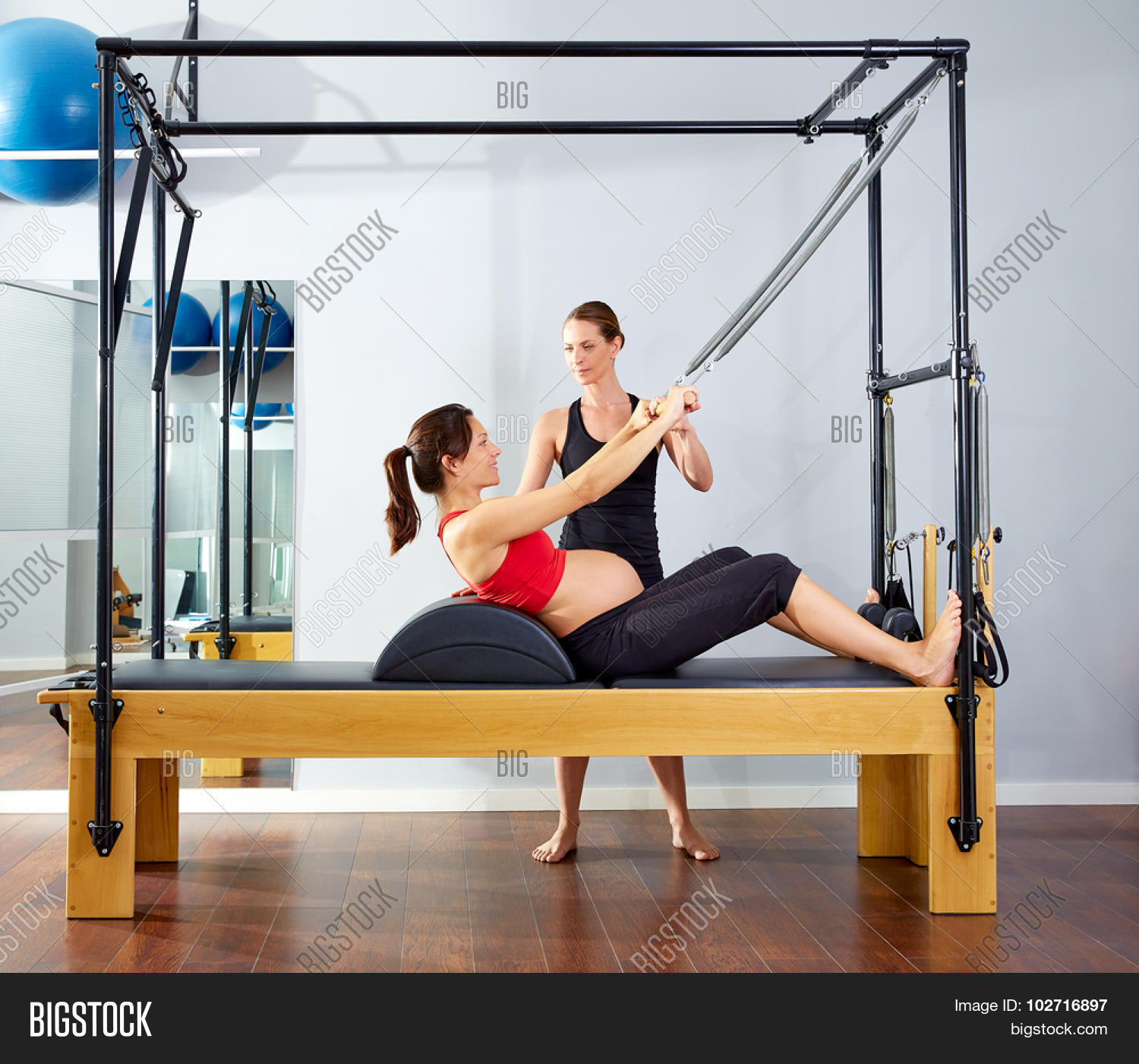 Pregnant Woman Pilates Reformer Roll Up Cadillac Exercise With Personal Trainer 102716897 Image Stock Photo