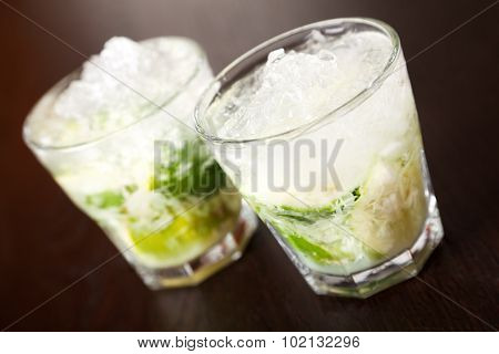 Two glasses of Caipirinha cocktail shot on a bar counter in a club stock photo