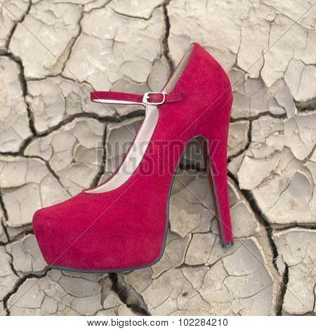 Textured desighn natural closeup background of cracked dry soil old grey ground in hot weather in droughty region with many splits and fissures with red suede high heeled shoe  ** Note: Shallow depth of field stock photo