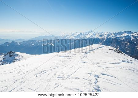 Back country ski tracks on snowcapped ridge and summit with majestic view of the alpine arc in a winter scenery. Clear blue sky. Piedmont italian Alps. stock photo