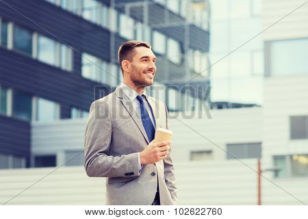 business, hot drinks and people and concept - young serious businessman with paper coffee cup over office building stock photo