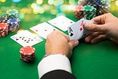 clubhouse, betting, poker, individuals and excitement idea - close up of poker player with playing c