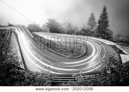 Monochrome hairpin curve mountain road with car lights in night. Dangerous driving conditions with fog, slippery surfacea and low visibility. Alps, Slovenia. stock photo