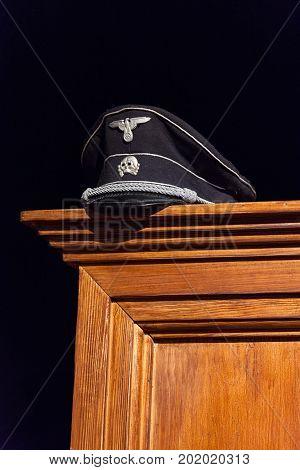 Nazi cap exhibited on wooden wardrobe on black background stock photo