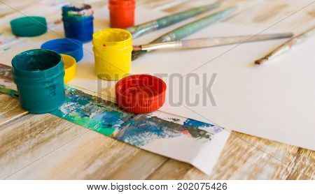 The workplace of the artist: watercolor paints paint brushes sheets of white paper color palette and unfinished painting stock photo