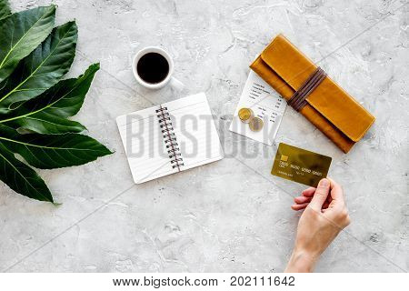 Pay the bills at restaurant. Hand hold coffee near bill, bank card and coins. Grey stone table top view.