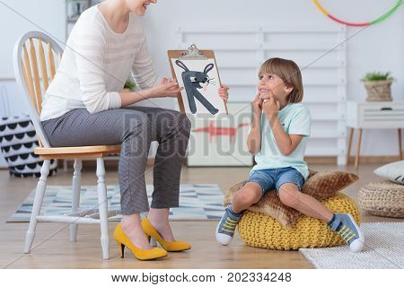 Boy doing exercise of correct pronunciation during a lesson with a speech therapist stock photo
