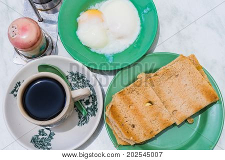 Singapore Breakfast called Kaya Toast Coffee bread and Half-boiled eggs Chinese coffee in vintage mug and bread toast with a local jam made from eggs sugar and coconut milk The fractal on the cup is generic print stock photo