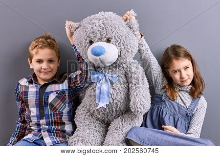 Two kids sitting with big teddy bear. Portrait of little brother and sister with big grey soft teddy bear. Kids family studio shot with soft toy. stock photo