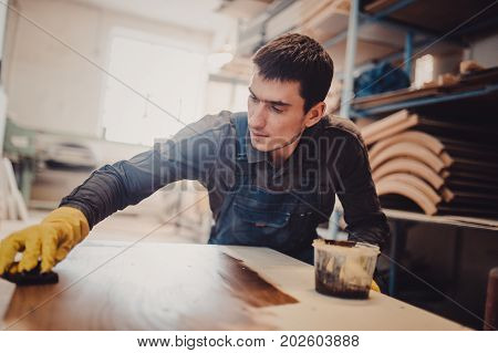 Carpenter is painting a wood with lacquer. The joiner covers the furniture with varnish in the production workshop of carpentry stock photo