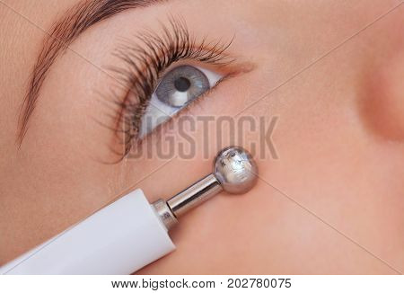 The cosmetologist makes the apparatus a procedure of Microcurrent therapy of a beautiful young woman in a beauty salon. Cosmetology and professional skin care. stock photo