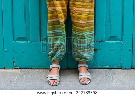 Feet of a woman in sandals with blue toe nails. Colorful hippie pants. Detail stock photo