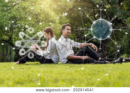 Happy asian couple using and listening the song and using the social network via smart mobile phone for online shopping with omni channel in the park lifestyle and technology concept stock photo