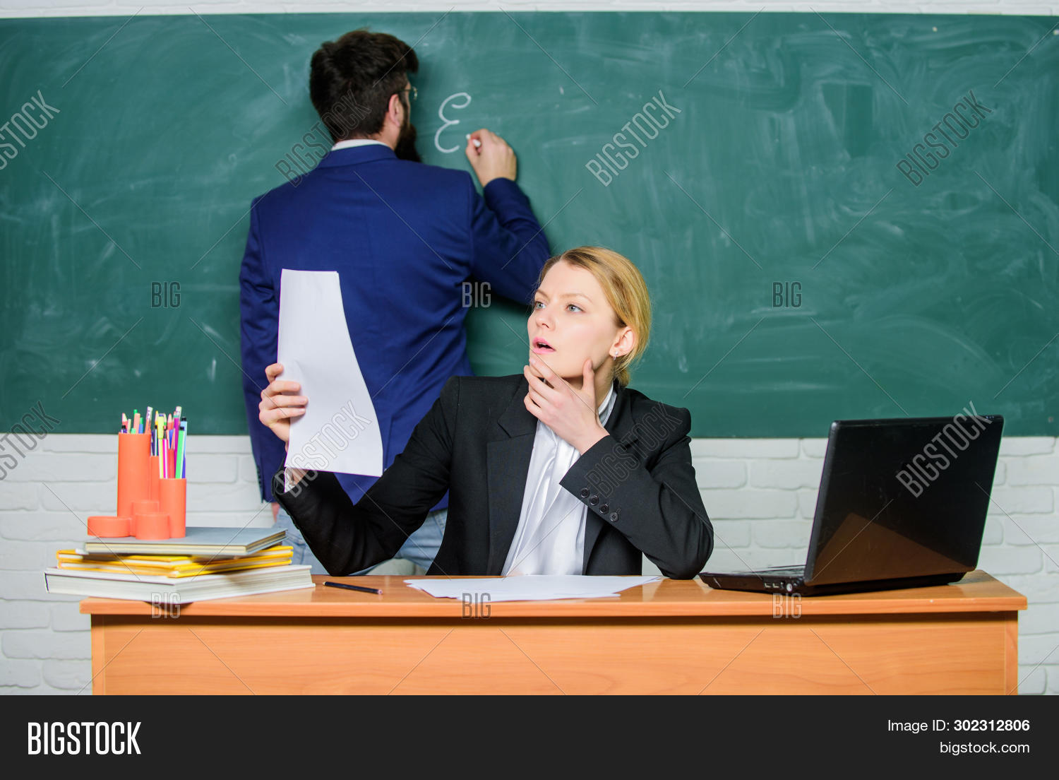 assistant,background,bearded,blackboard,caucasian,chalkboard,check,classroom,colleagues,computer,concept,documents,down,education,educational,educator,examination,formal,handsome,homework,knowledge,laptop,lesson,man,notebook,pairs,prepare,program,report,school,september,study,subject,supervisor,task,teach,teacher,test,trainee,woman,working,write,your