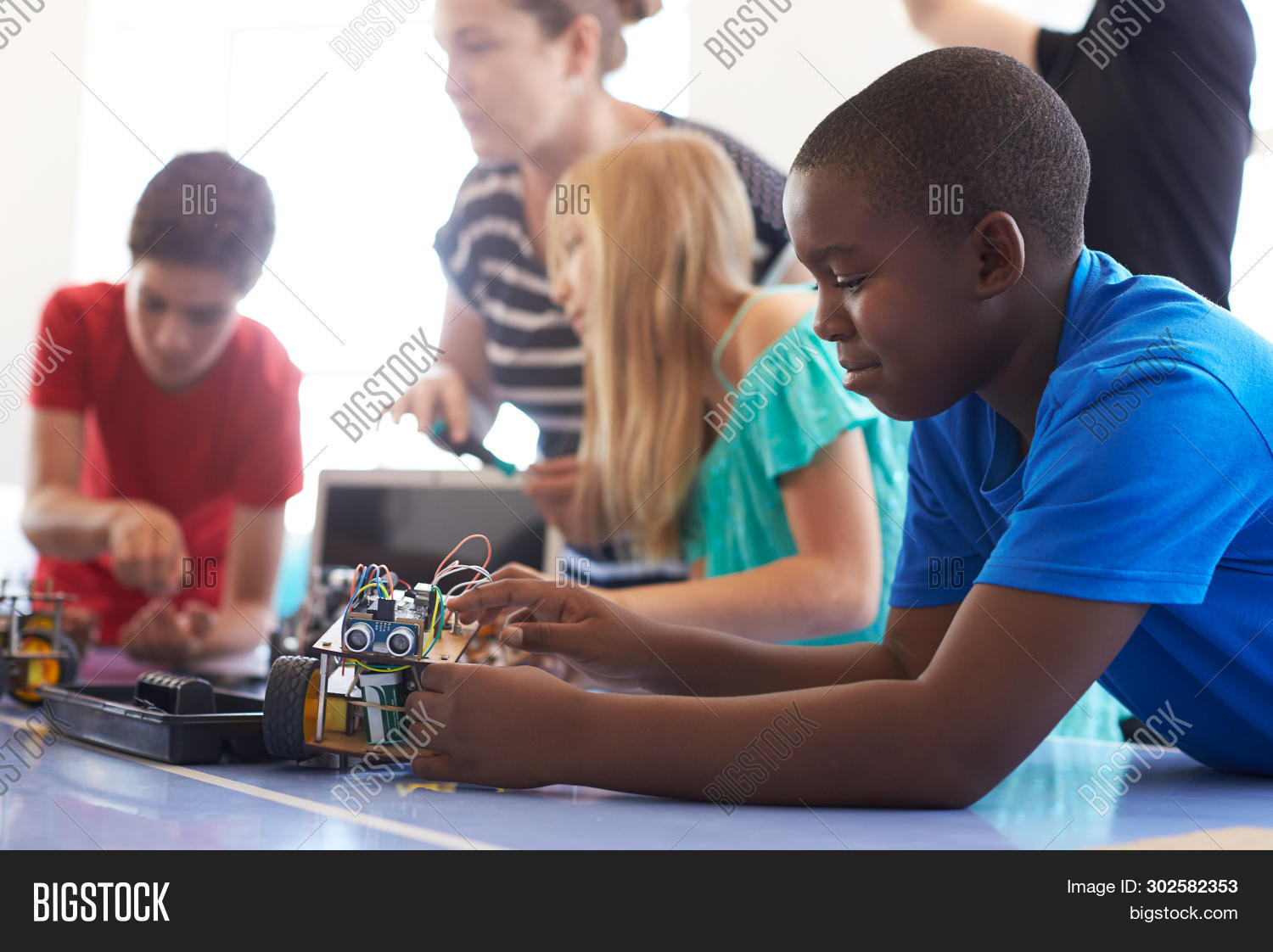 10 years old,11 years old,african american,after school,black,boy,building,car,caucasian,child,children,class,club,code,coding,computer,computing,education,female,five people,girl,grade school,group,helping,horizontal,laptop,learning,lesson,listening,making,male,middle school,multi-cultural,people,person,programming,pupils,robot,robotics,school,stem,students,teacher,teaching,technology,tutor,vehicle,woman,women
