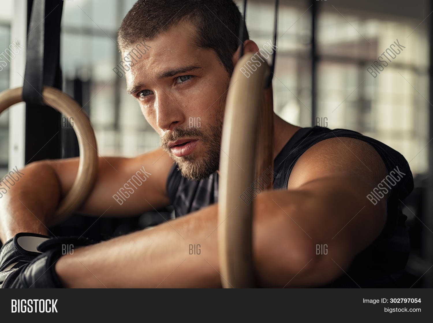 Closeup of young man resting after gymnastic ring exercise at crossfit gym. Fitness guy thinking whi
