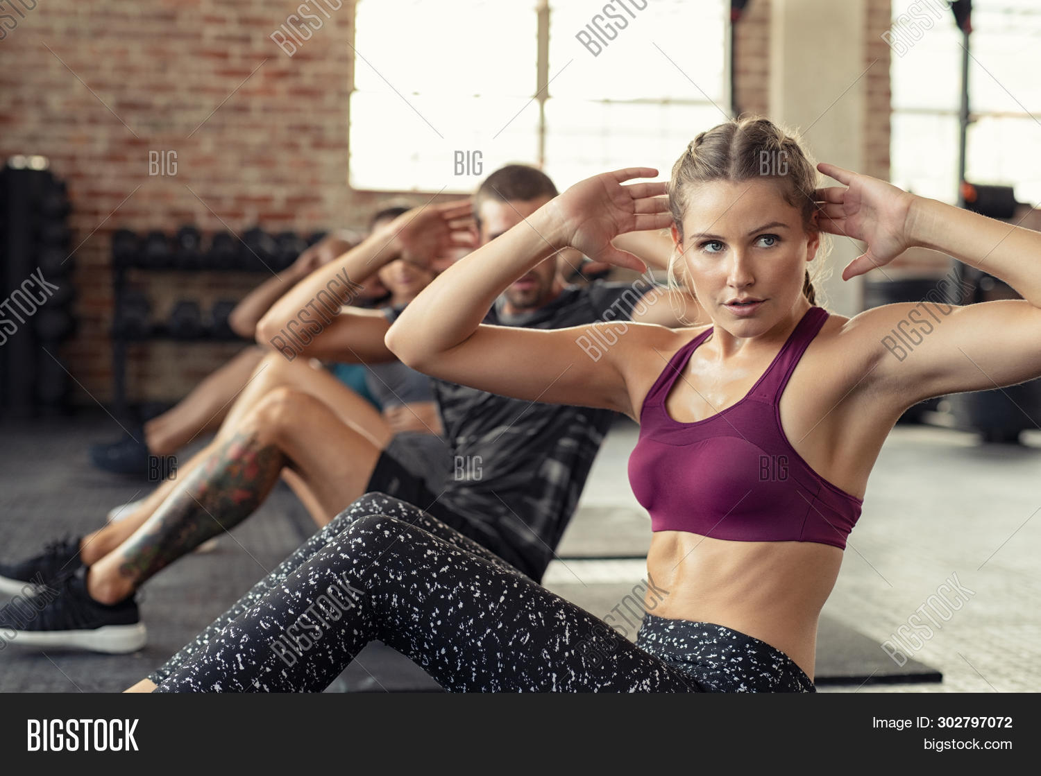 Young fitness woman doing abdominal exercise at gym. Concentrated people in a row doing sit ups on y