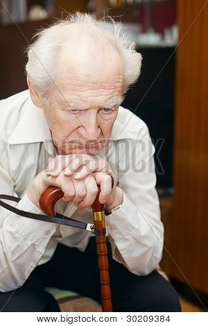 sitting unhappy old man holding his cane stock photo