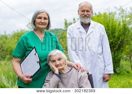 Aged woman with dementia sitting in a wheelchair, male doctor and female nurse taking care of her outdoor - assisted living stock photo