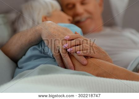 Close-up of aged nice-appealing good-looking loving aged couple holding hands stock photo