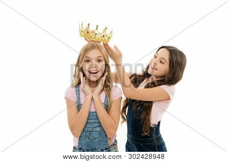 Rich reward. Little girl putting crown on head of small beauty queen winner as reward. Adorable mini miss beauty pageant winner taking reward for success. Awarding with prize and reward. stock photo