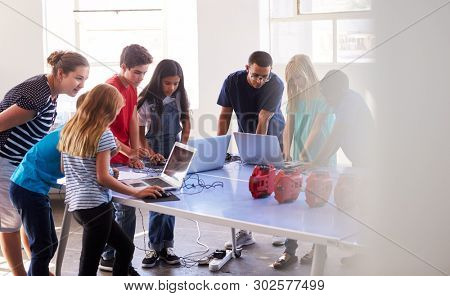 Group Of Students In After School Computer Coding Class Learning To Program Robot Vehicle stock photo