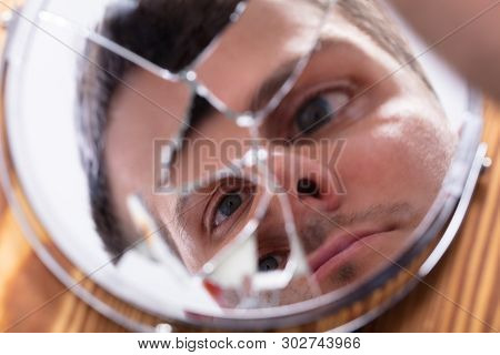 Close-up Of Young Man Looking At His Face In A Broken Mirror stock photo