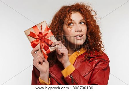Portrait of adorable redhead woman 20s wearing leather jacket smiling and holding gift box isolated over white background stock photo