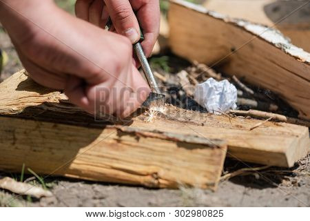 A pair of hands making a fire with flint and steel stock photo
