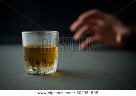 glass of whiskey or cognac or alcohol drink, hand of a drunk man in the background, alcoholism and alcohol abuse concept, defocused, selective focus, close up, gray table, dark background stock photo