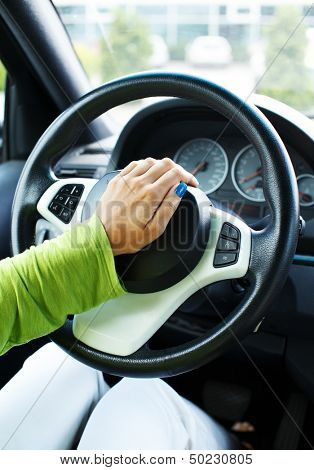 Woman hand pressing on a car horn  stock photo