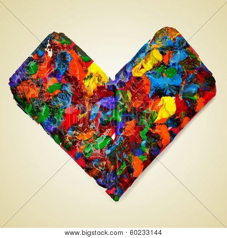 a heart splashed with paint of different colors on a beige background with a retro effect stock photo