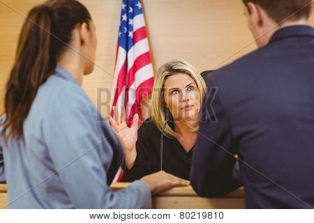 Judge and lawyers speaking in front of the american flag in the court room stock photo