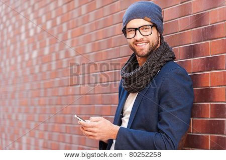 Side view of handsome young man in smart casual wear holding mobile phone while leaning at the brick wall stock photo