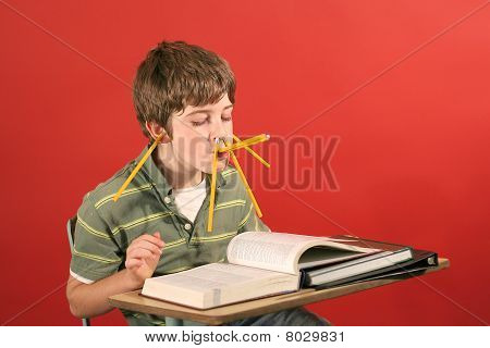 shot of a kid goofying off while studying stock photo