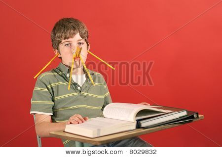 shot of a kid showing off being silly with pencils stock photo
