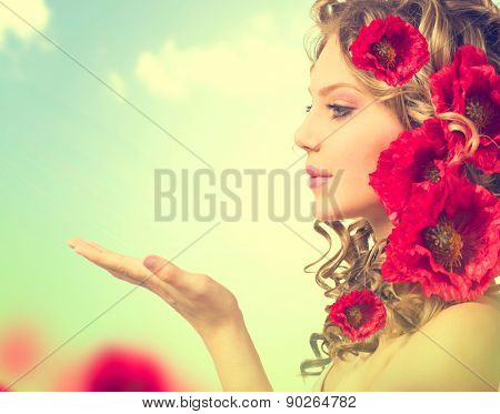 Beauty girl with red poppy flowers hairstyle and open hands. Blowing flower. Hairstyle with flowers.